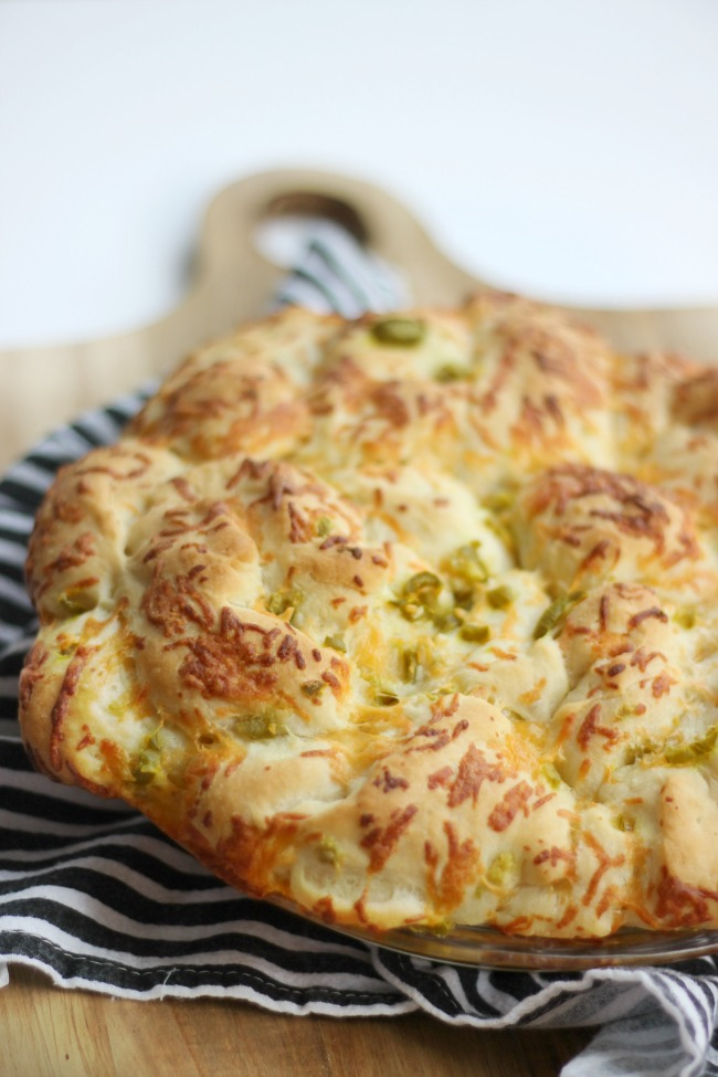 jalapeño cheese bread sitting on cutting board to cool