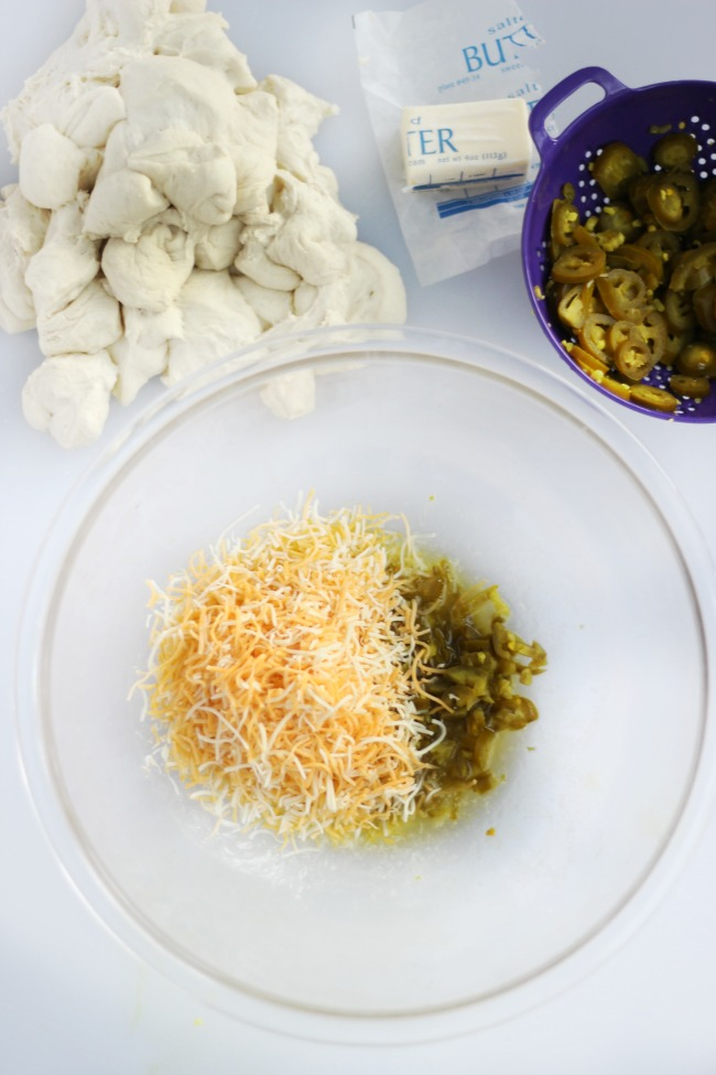 large glass bowl with shredded cheese, diced jalapeños and shredded cheese