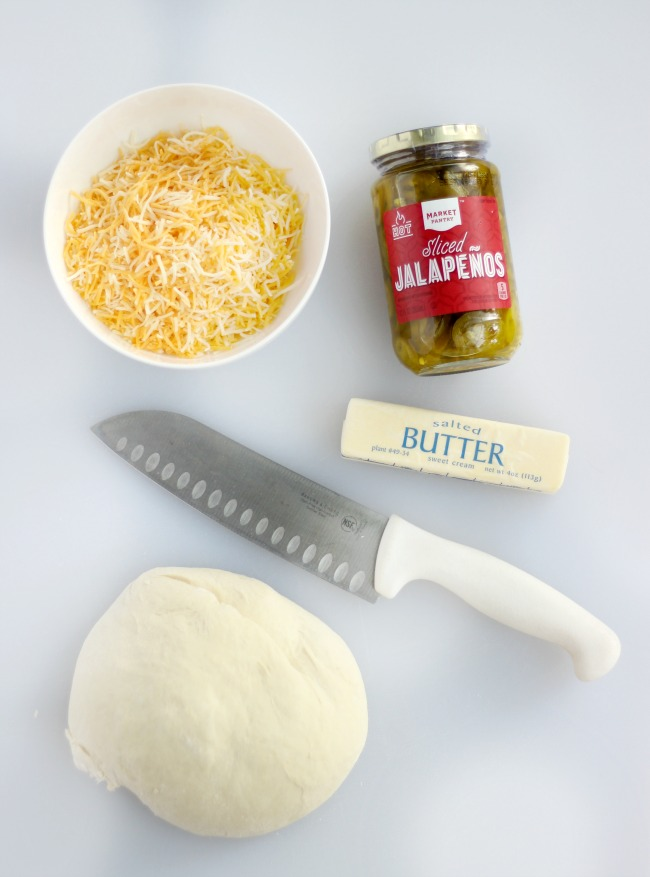 picture of a bowl of cheese, jar of japapeños, a knife, a stick of butter and a ball of bread dough