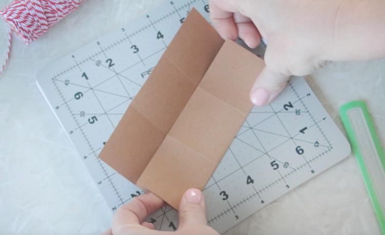 hands folding paper along scored lines