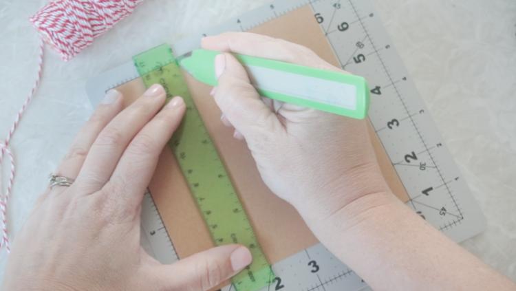 hands using scoring tool to score paper