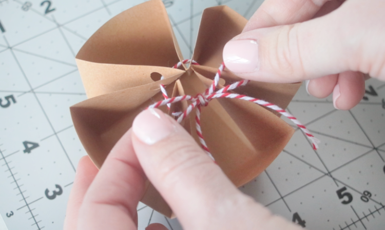 hands tying twine into bow