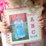 little girl holding alphabet book