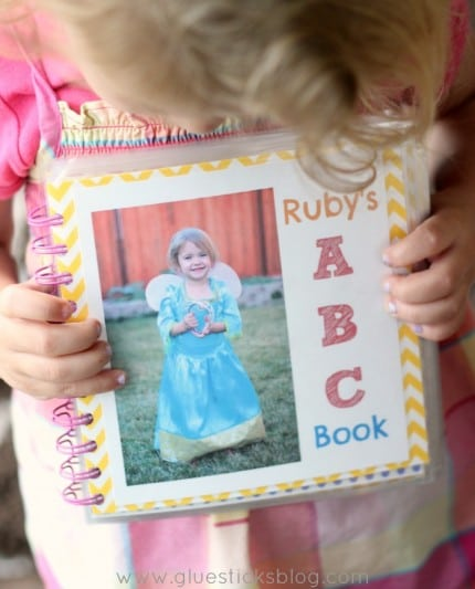 little girl holding personalized abc book