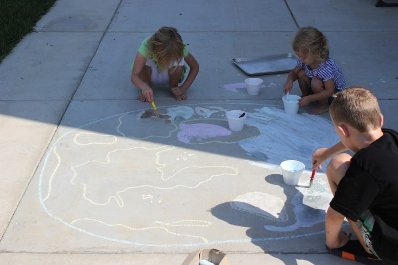 kids chalk painting a continent on the ground