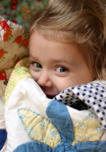 little girl wrapped in quilt