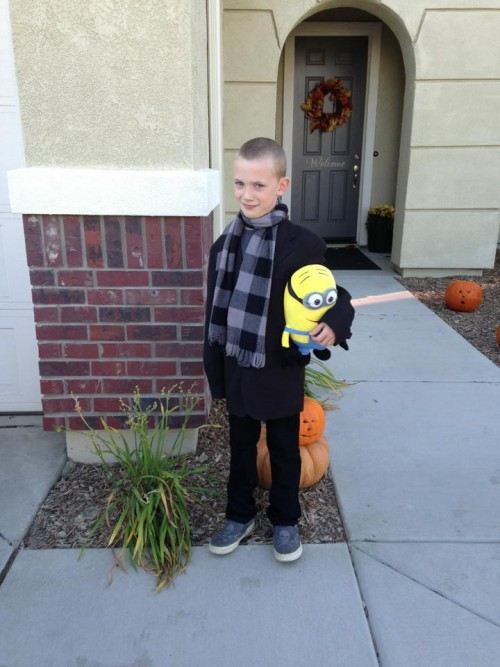 little boy in Gru costume holding a minion toy