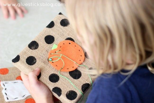 little girl sewing through felt