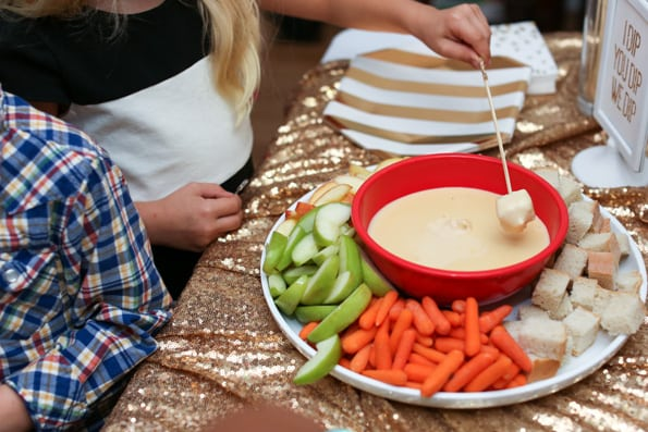 gold sequin table cloth on table with cheese fondue and children dipping bread