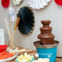 chocolate fondue on table with fixing
