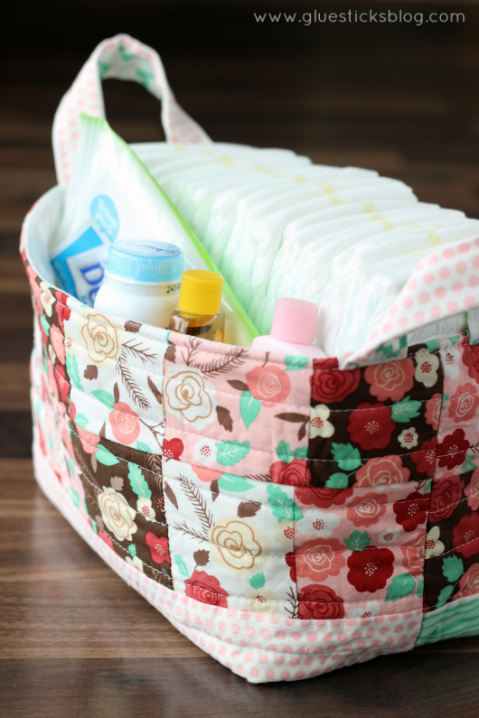fabric gift basket with diapers and baby supplies inside
