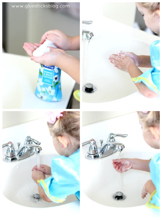 child washing hands with soap in sink