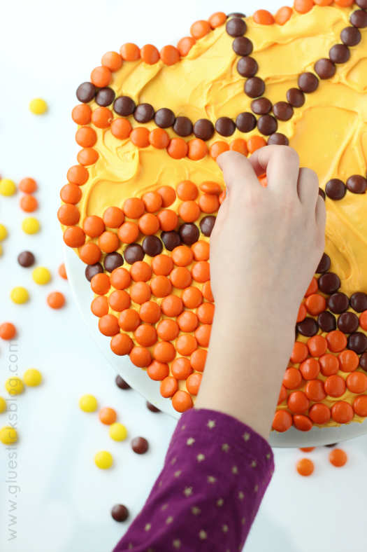 child helping add candies to pull apart basketball cake