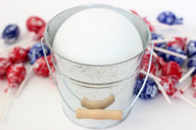 BBQ season is upon us and with Memorial Day and the 4th of July just around the corner, here is a fun patriotic lollipop topiary that the kids will love! I can guarantee that if you bring this to your next gathering it will be the hit of the party! A quick and easy lollipop topiary made in about 10 minutes.