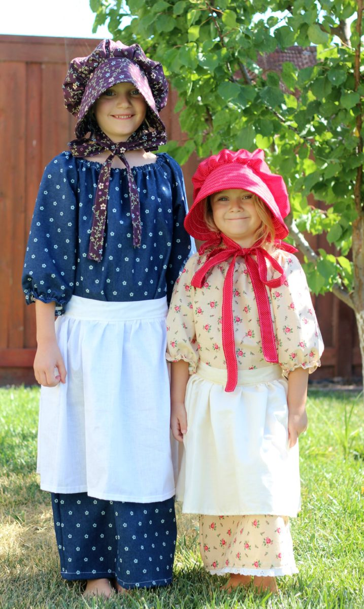 two little girls wearing pioneer costumes