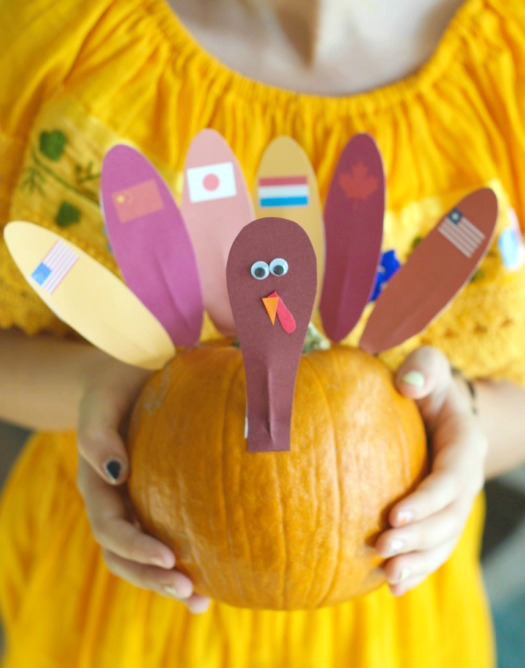 little girl with turkey pumpkin