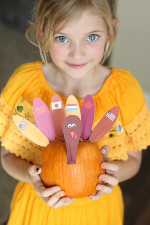 little girl holding thanksgiving around the world pumpkin