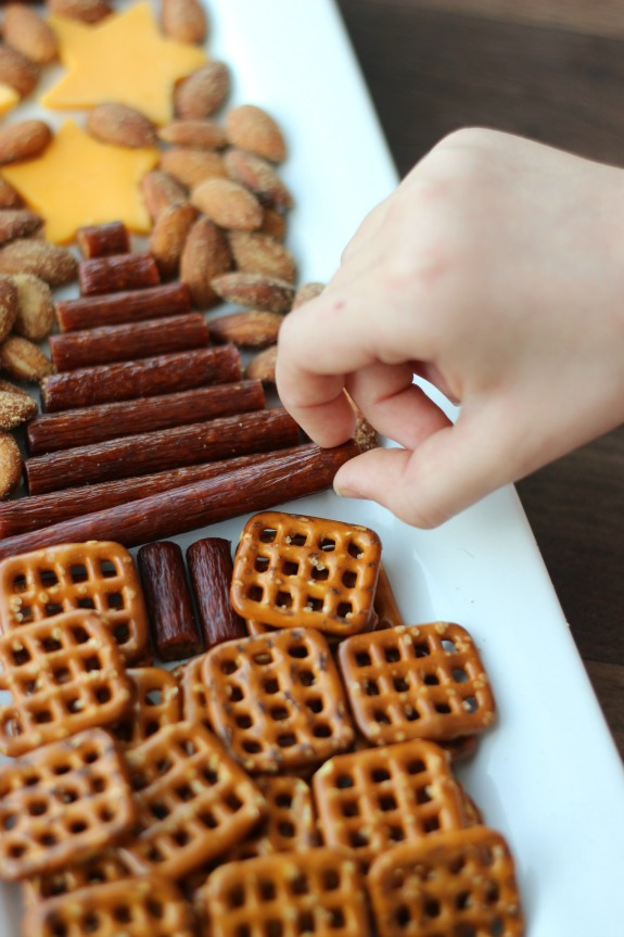 An easy snack tray to serve during the holidays made with sausage, cheese, nuts, and nuts in the shape of a tree. A yummy savory alternative to sweet treats.