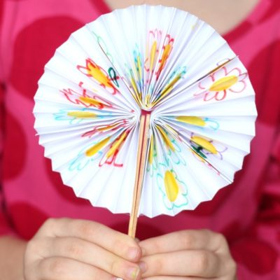 child holding paper fan