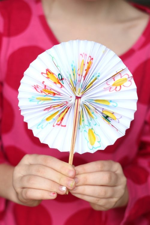child holding homemade paper fan