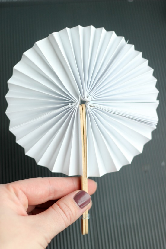 This DIY pocket fan fold up & store perfectly in a pocket for hot days. It is such a unique and fun craft idea for kids! They can decorate the front with simple artwork then secure with popsicle sticks & a rubber band!