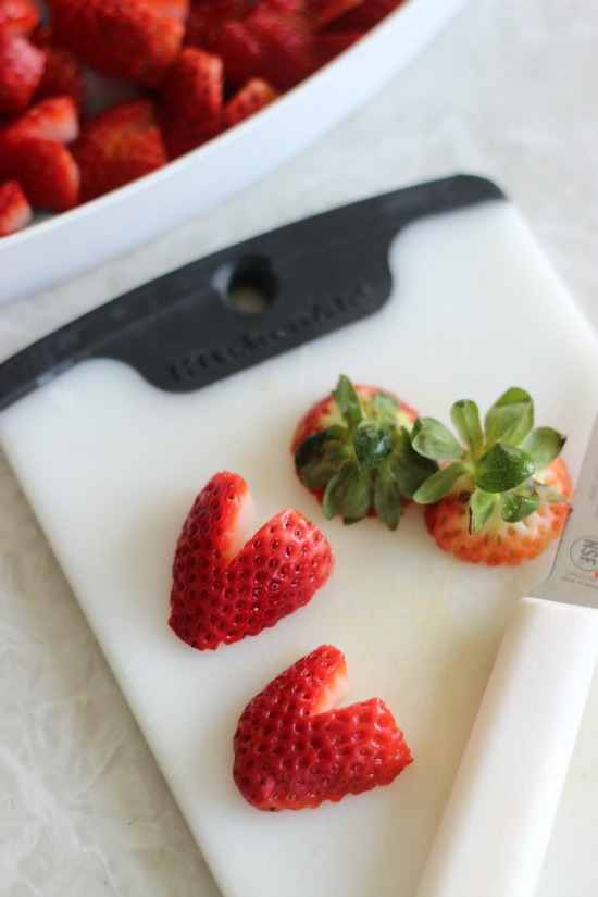cutting board with sliced heart strawberries
