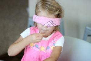 blindfolded child trying a piece of candy