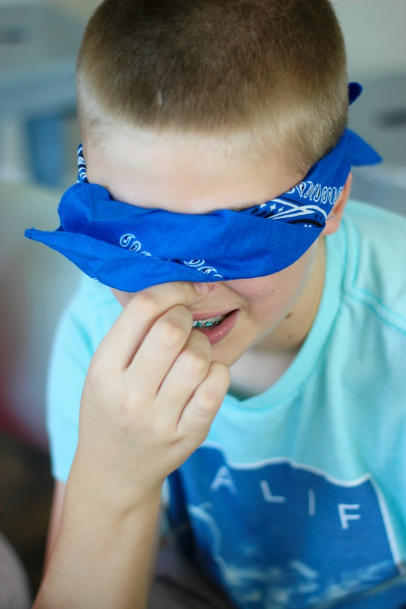 child with blindfold and plugged nose eating candy