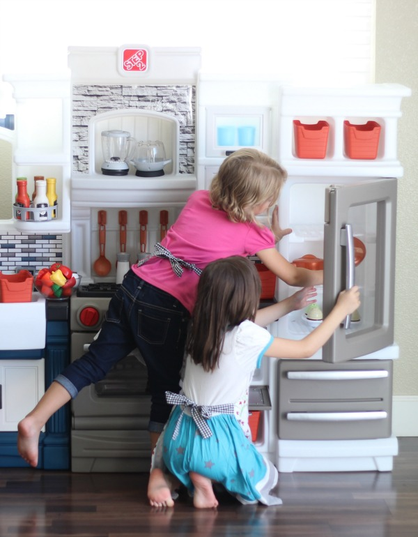 children wearing aprons playing in kitchen