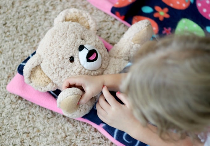 child putting teddy bear in sleeping bag