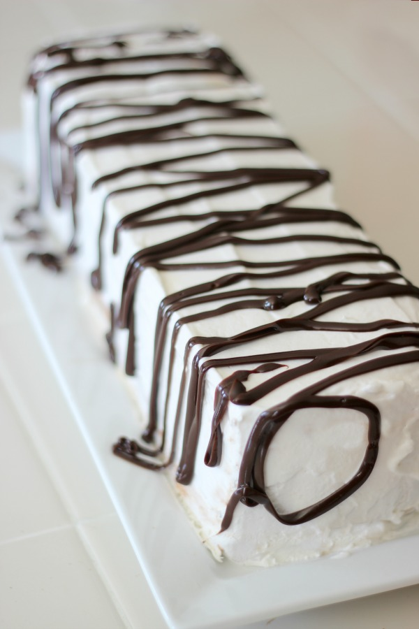 This ice cream sandwich cake is SO easy to make! Chocolate ice cream sandwiches stacked, frosted in whipped topping, and drizzled with hot fudge.