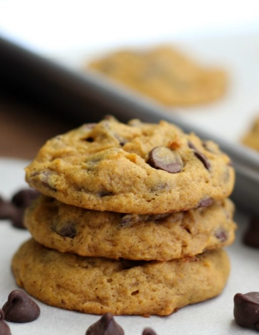 3 pumpkin chocolate chip cookies stacked on parchment paper