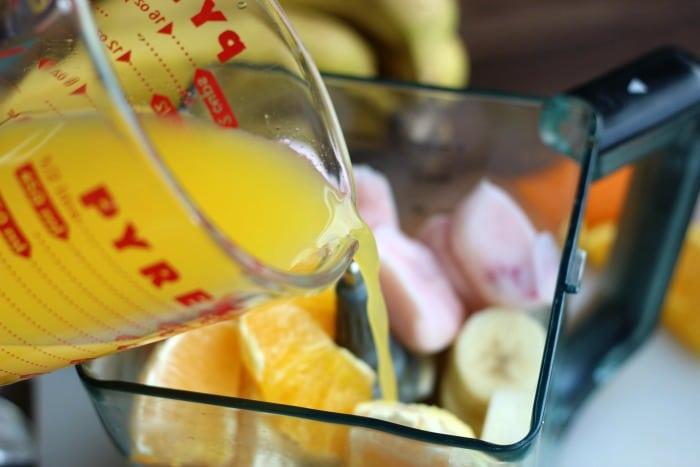 orange juice poured into blender for smoothie