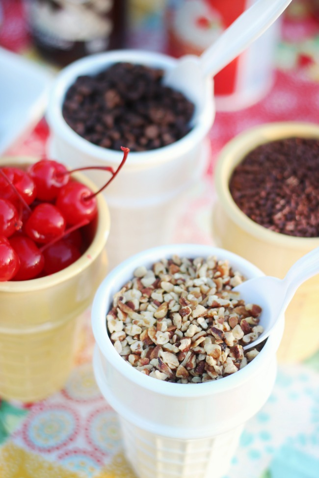 bowls of toppings for cookie sundae party. nuts, cherries, chocolate chips.
