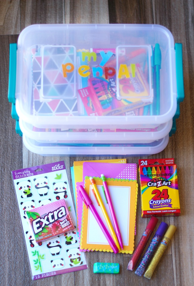 3 pen pal totes stacked on top of each other with assortment of stationary supplies next to them.