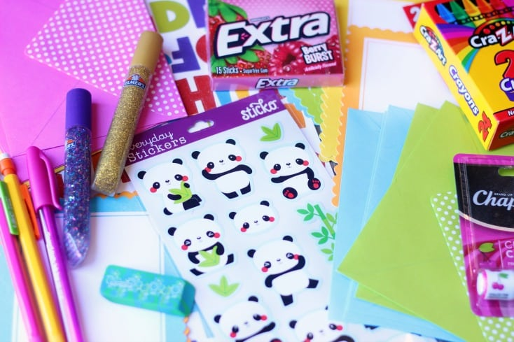 assortment of stationary, stickers, pencils, crayons and glitter glue tubes