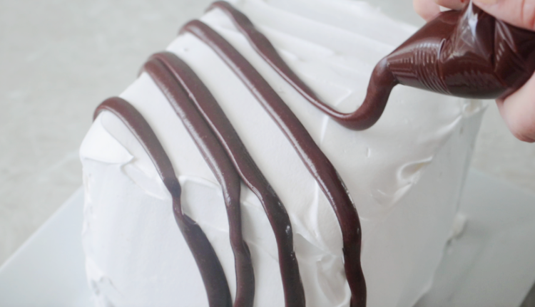 bag of hot fudge drizzled over cake