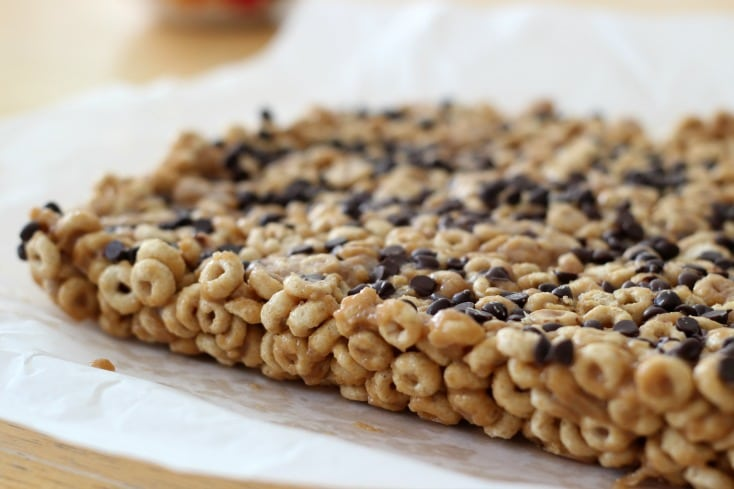 Peanut Butter Cheerio Bars! A delicious after school snack made with peanut butter, honey, a bit of sugar, and Honey Nut Cheerios™! Sprinkle with mini chocolate chips if you're feeling crazy.