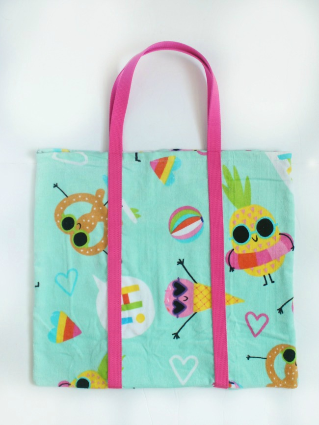 A DIY beach bag made out of a beach towel! Grab a fun and funky towel and let's get started! The perfect bag for towels, sunscreen, and treats to share with friends at the pool this summer!