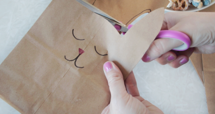 hand cutting around bunny ears with scissors