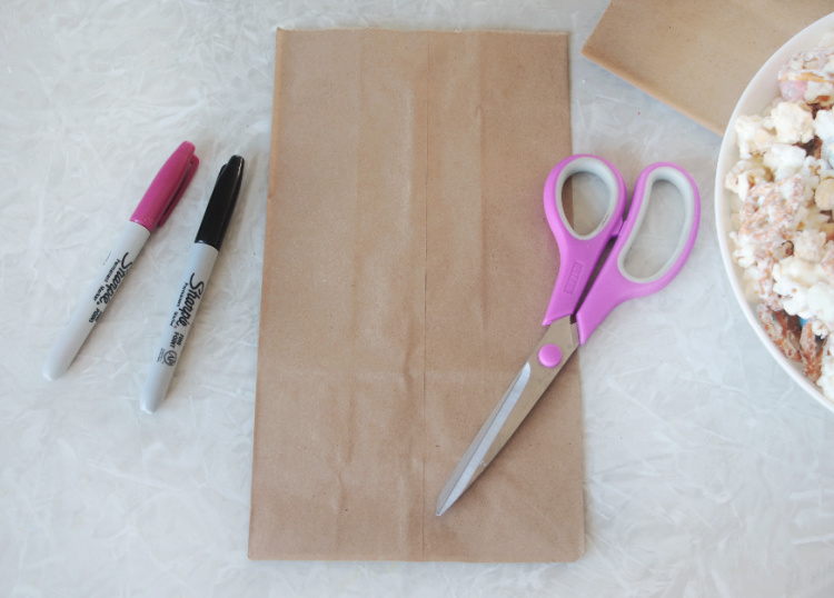 two permanent markers, scissors and a brown bag on table