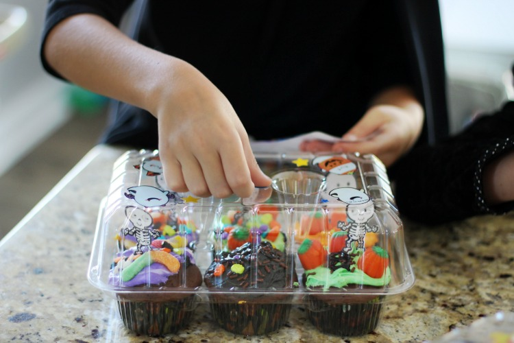 child decorating cupcake tray with stickers at halloween cupcake decorating party