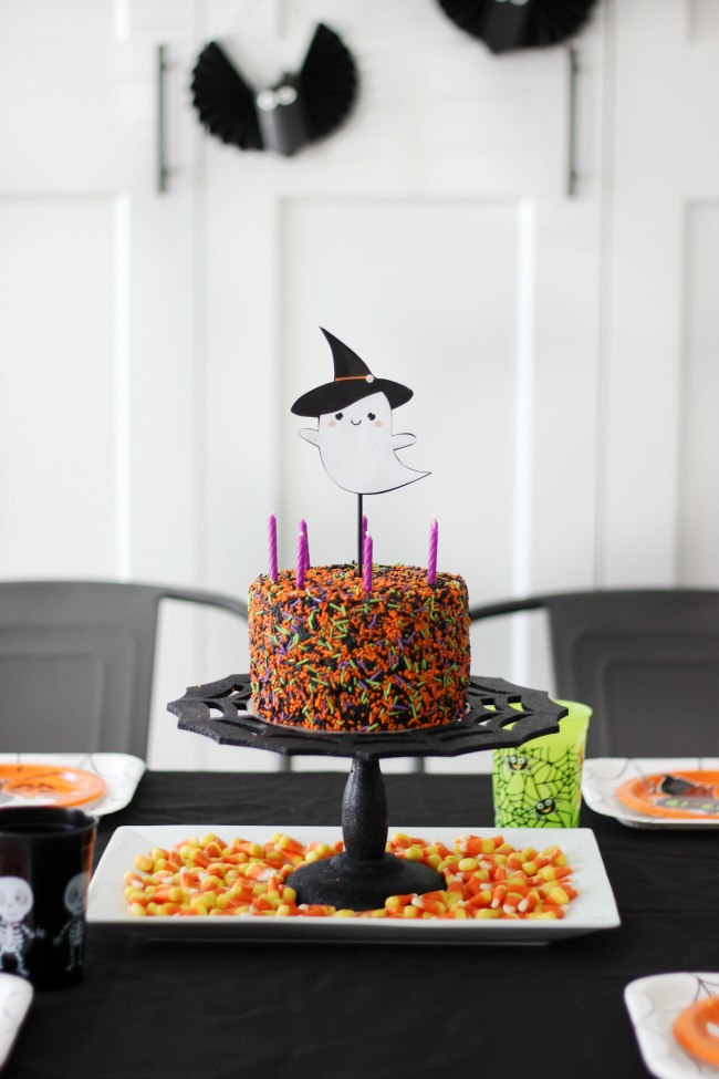 small halloween sprinkles cake on table with black table cloth