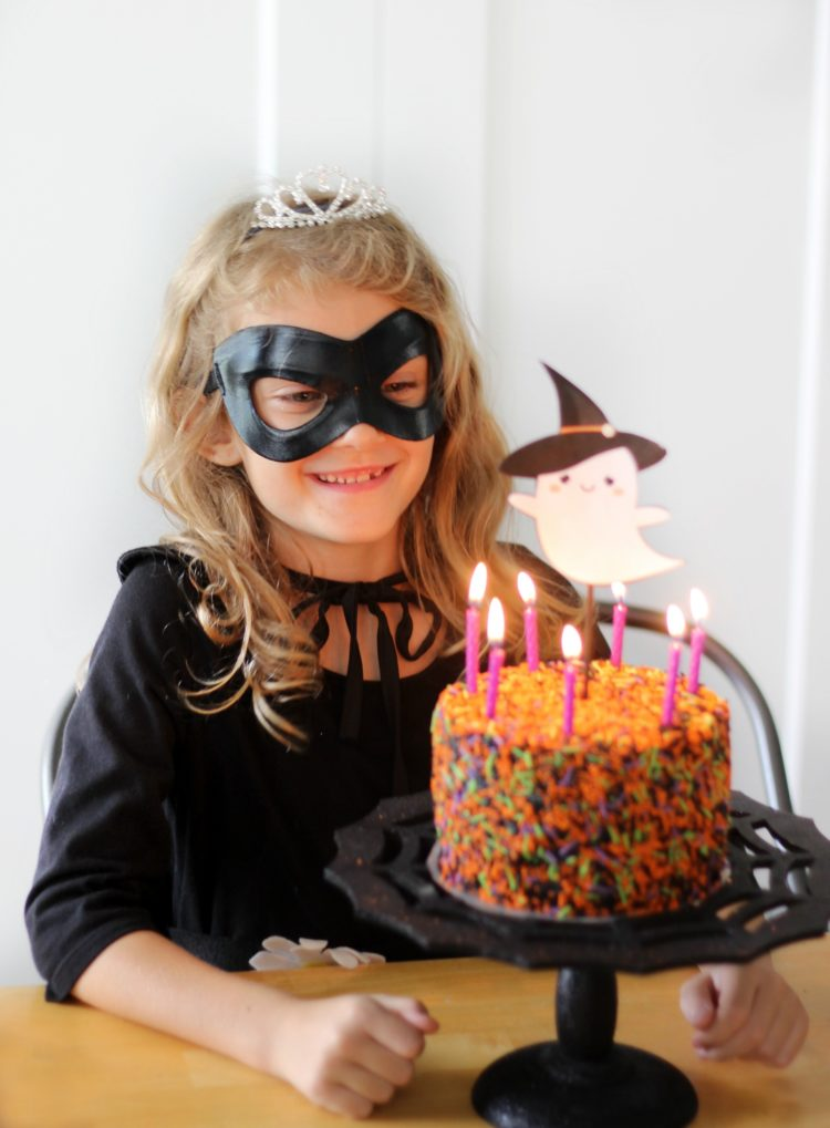 child with cake and lit candles for birthday