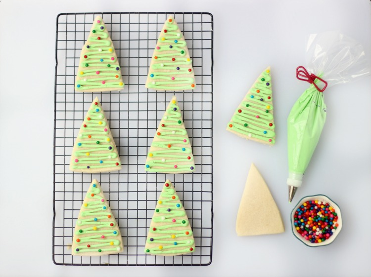 tree sugar cookies on baking rack with bowl of sprinkles and icing tube