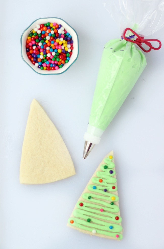 baked sugar cookie with frosting tube and bowl of sprinkles