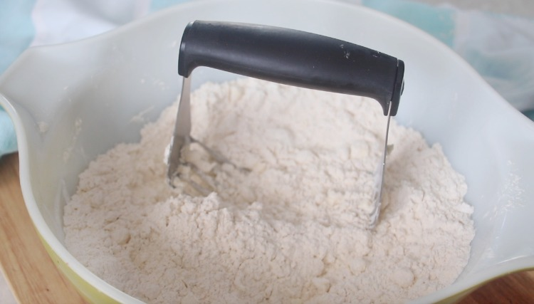 pastry cutter in bowl of flour and butter
