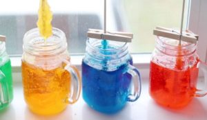3 jars of colored syrup in jars sitting on window sill