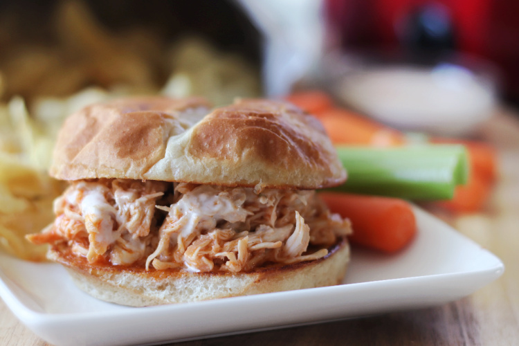 buffalo chicken sandwich with potato ships and carrots