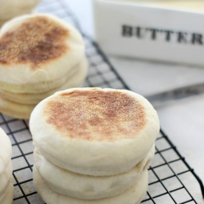 3 english muffins stacked on cooling rack